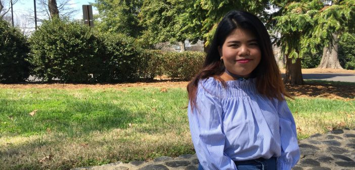 Uyen Nguyen sitting outside on campus
