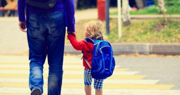 Dad walking with daugther wearing backpack